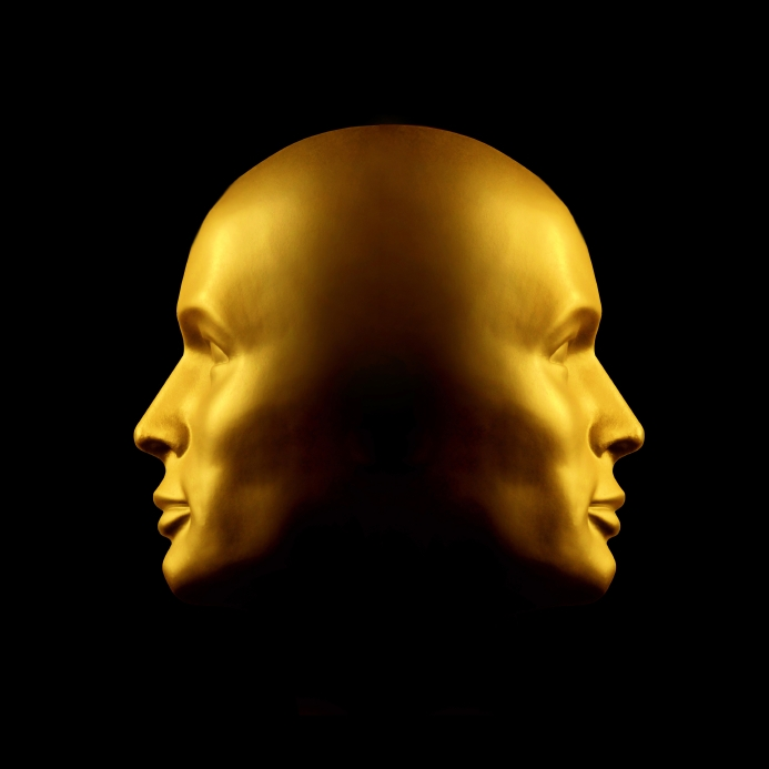 Two faced gold head statue against black